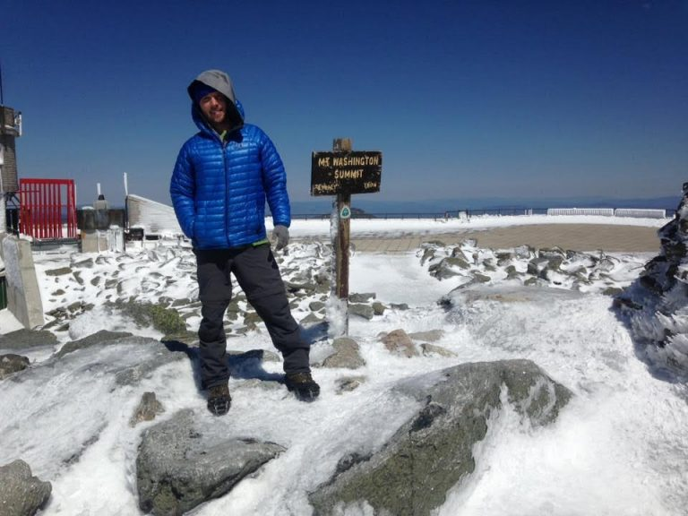 Justin Walsh standing on the summit of Mt. Washington in NH, home to the world's worst weather.