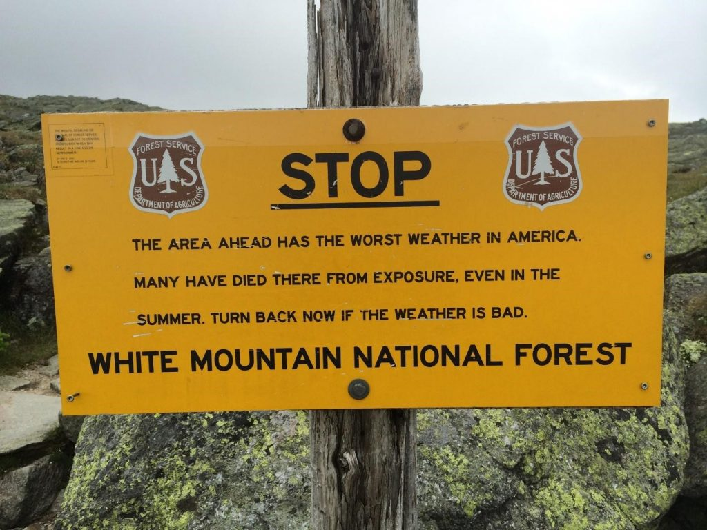 Sign: Stop! The area ahead has the world's worst weather in America. White Mountain National Forest.
