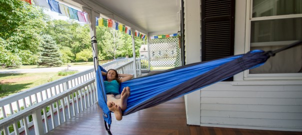 Girl lying in hammock on front porch of the Notch Hostel, White Mountains, NH